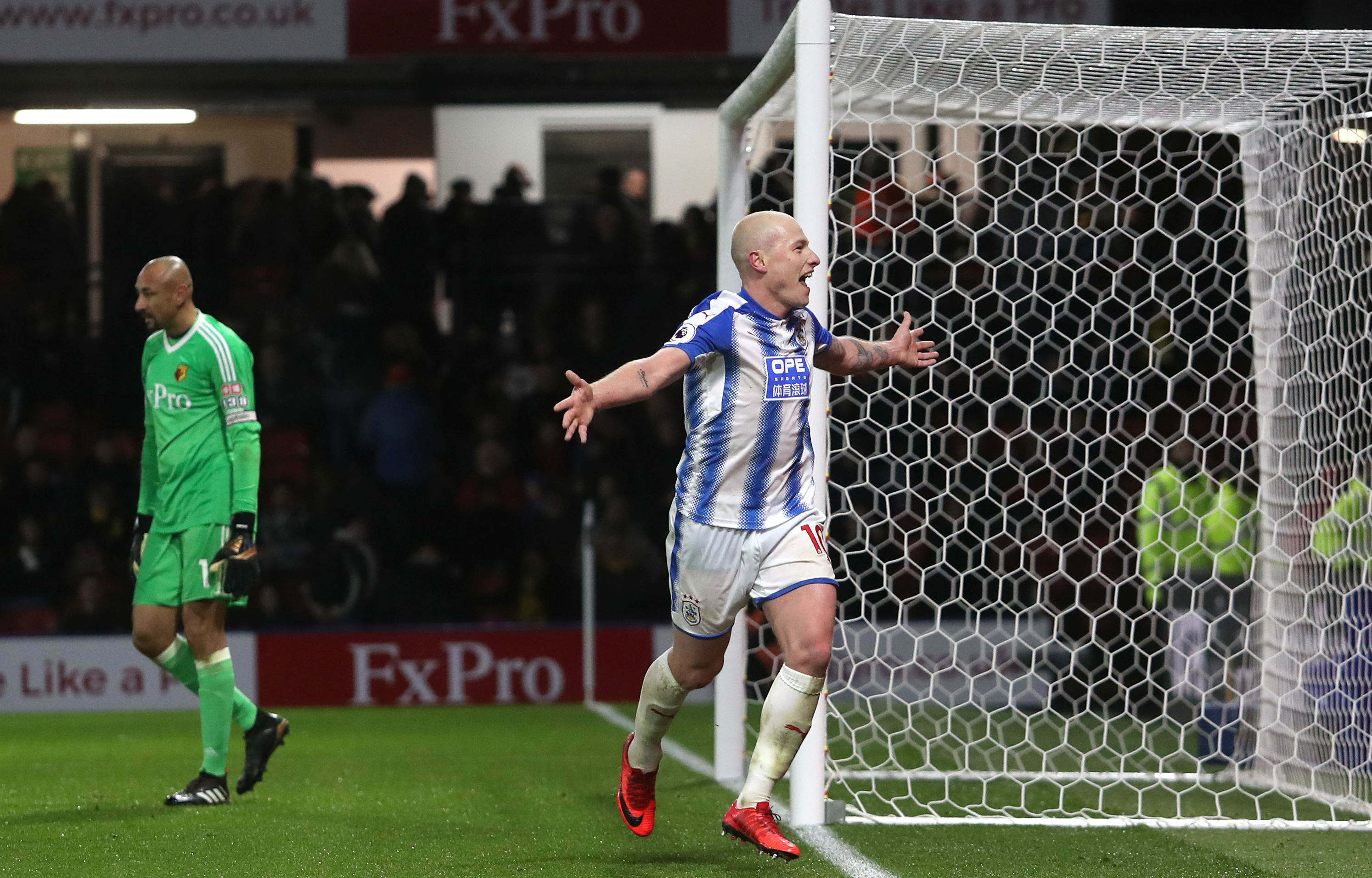 Aaron Mooy celebrates after converting a late penalty for Huddersfield.