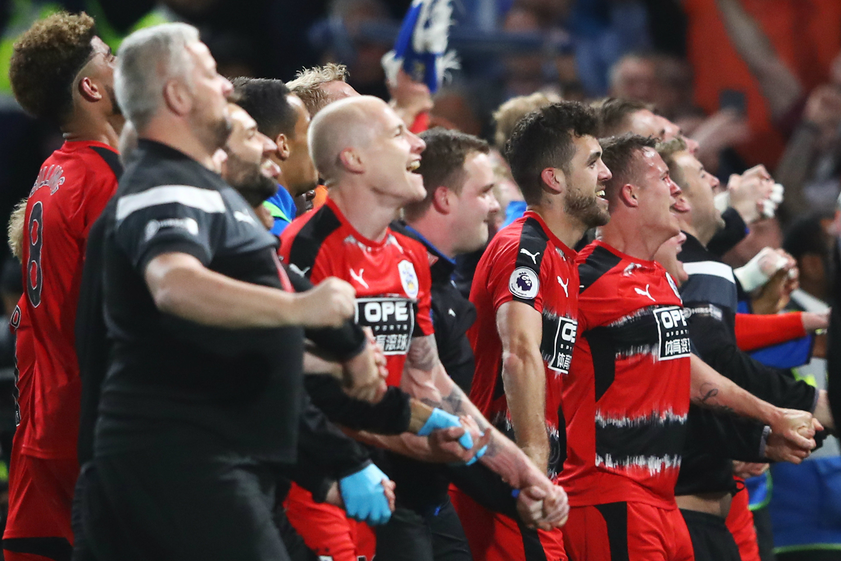 Aaron Mooy and his Huddersfield teammates celebrate avoiding relegation.