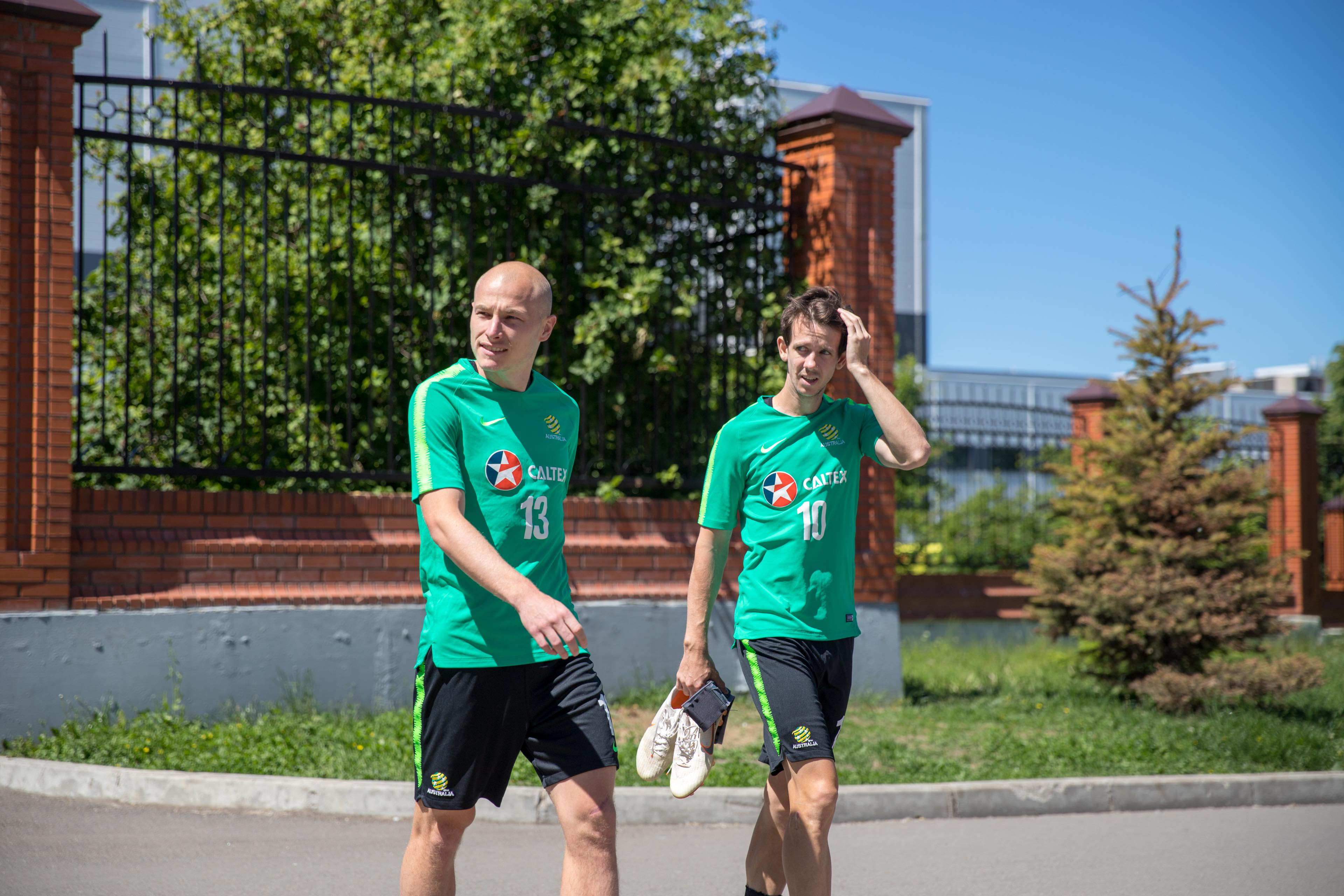 Aaron Mooy and Robbie Kruse walk to training in Kazan