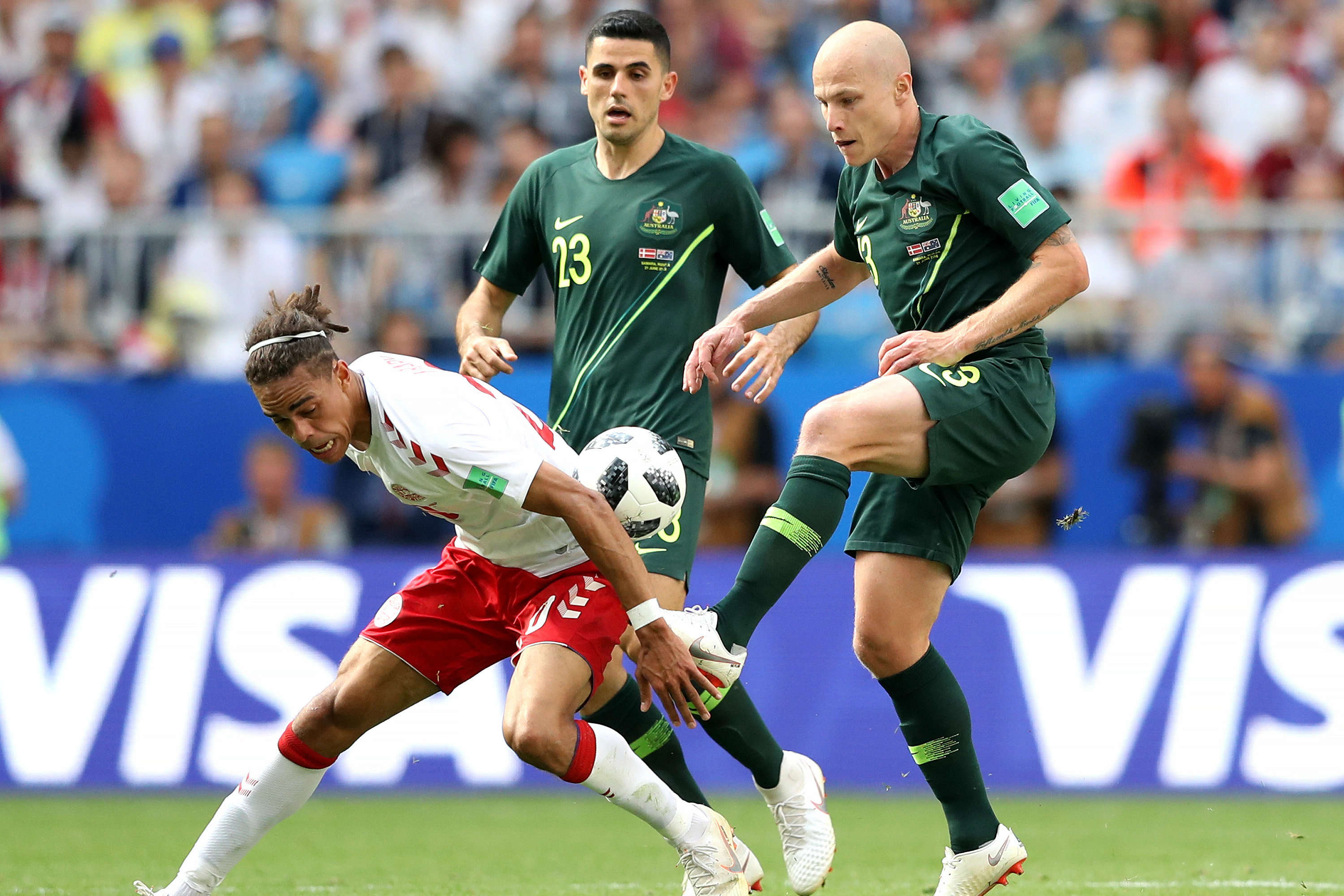 Aaron Mooy wins the ball from Denmark's Yussuf Poulsen.