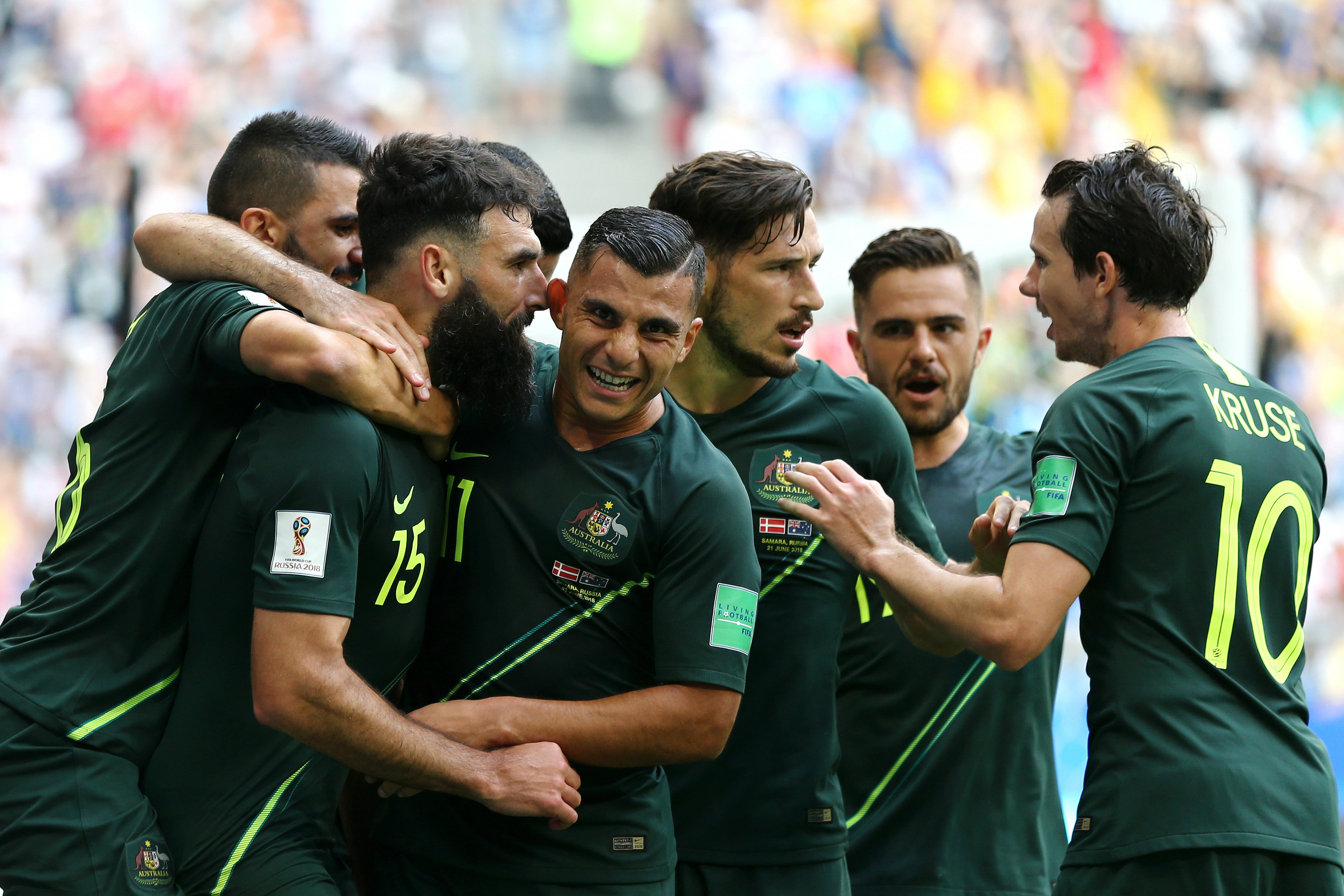Australian players get around Mile Jedinak after his goal.