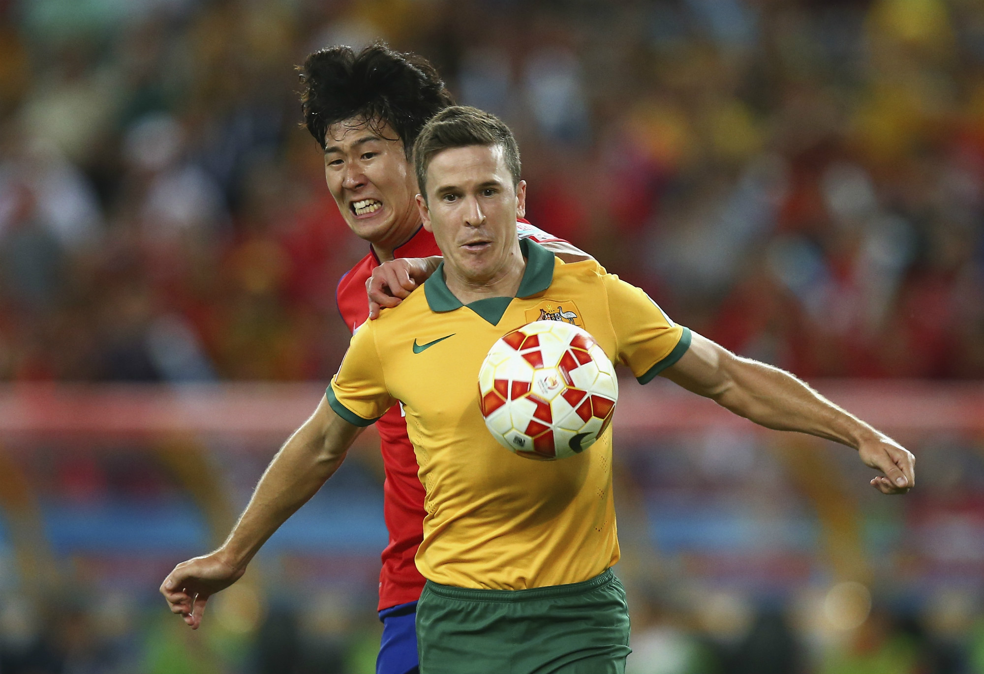 Matt McKay, playing for the Caltex Socceroos, is pressured by Son Heung-min