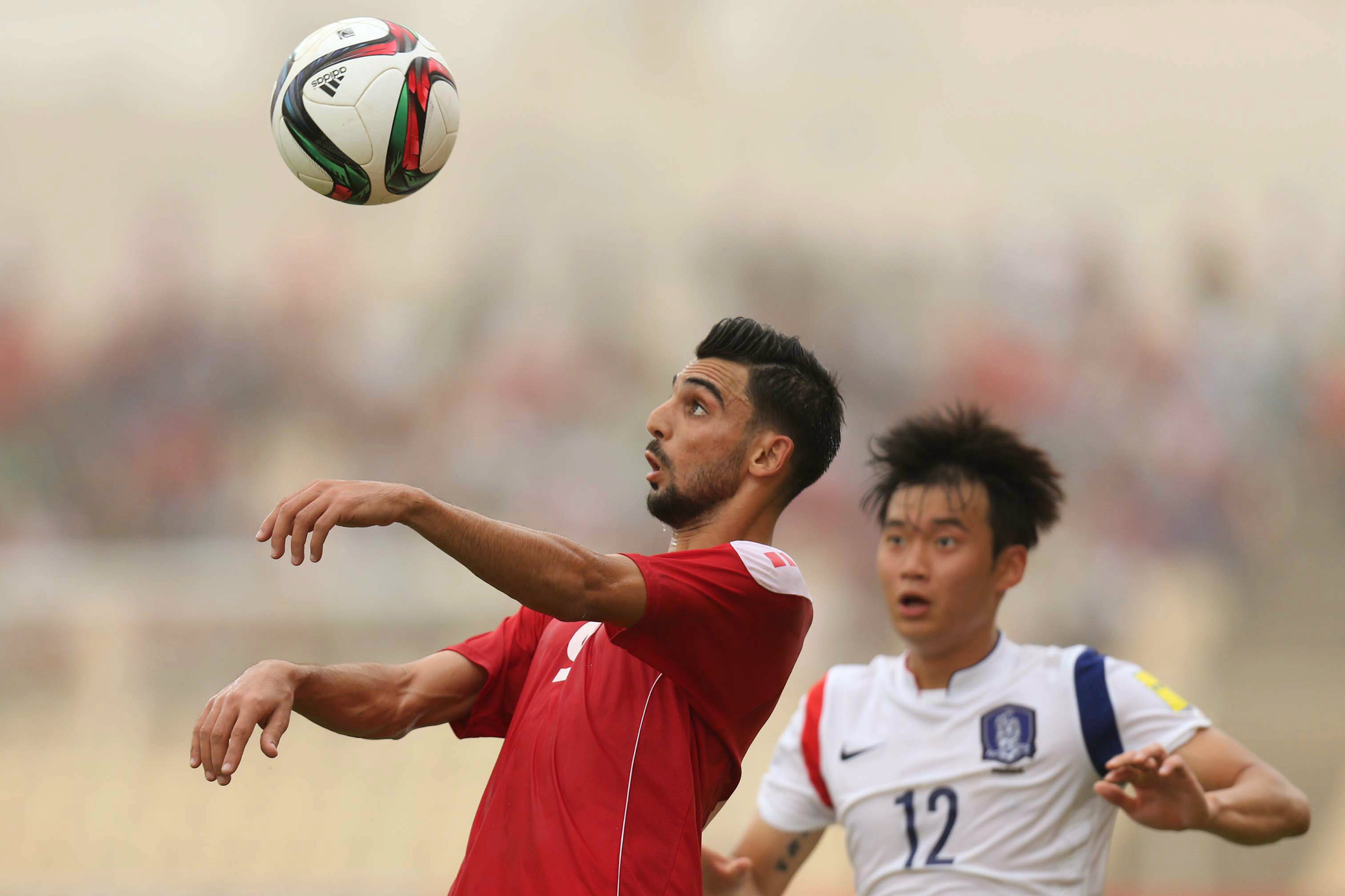 Mohamed Haider heads the ball against Korea Republic.