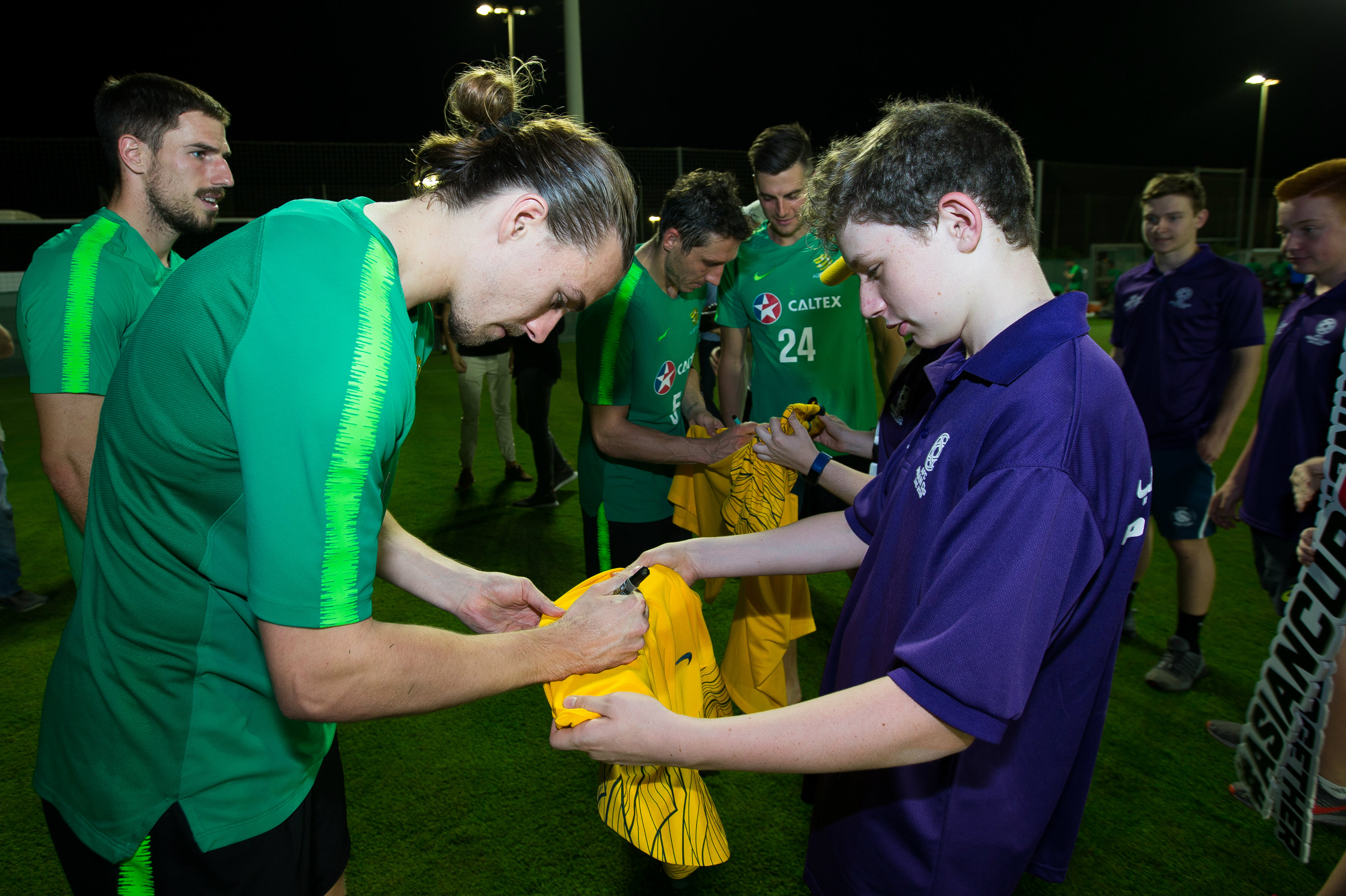 Jackson Irvine signs a jersey for a young fan.
