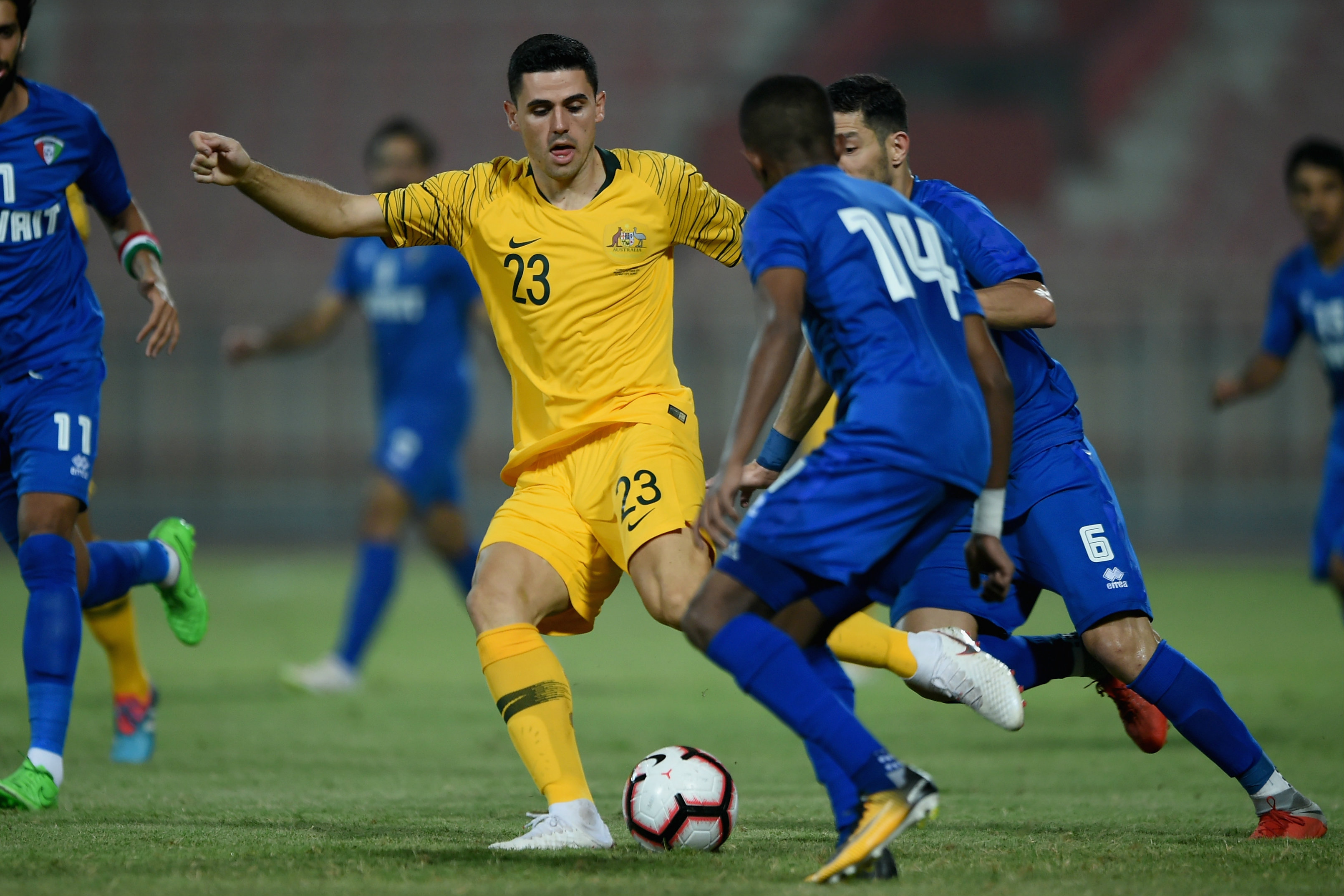 Tom Rogic tries to wriggle free of a couple of Kuwait defenders.