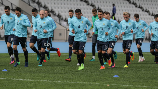 The Caltex Socceroos go on a warm-up jog during their open training session in Melbourne on Sunday.