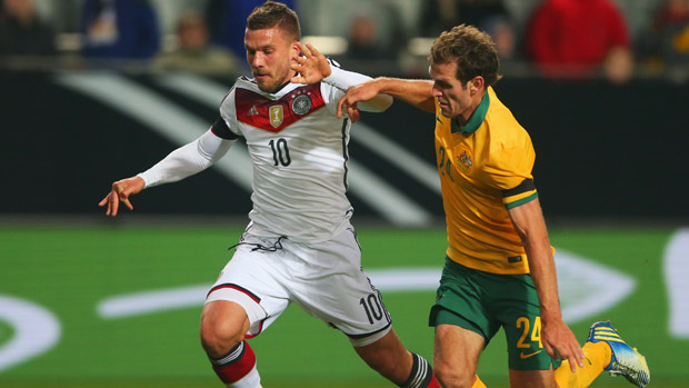 Luke DeVere challenges Germany striker Lukas Podolski.