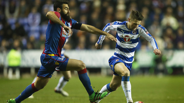 Crystal Palace skipper Mile Jedinak challenges for the ball with Reading's Oliver Norwood.
