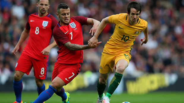 Robbie Kruse controls the ball in front of Jack Wilshere.