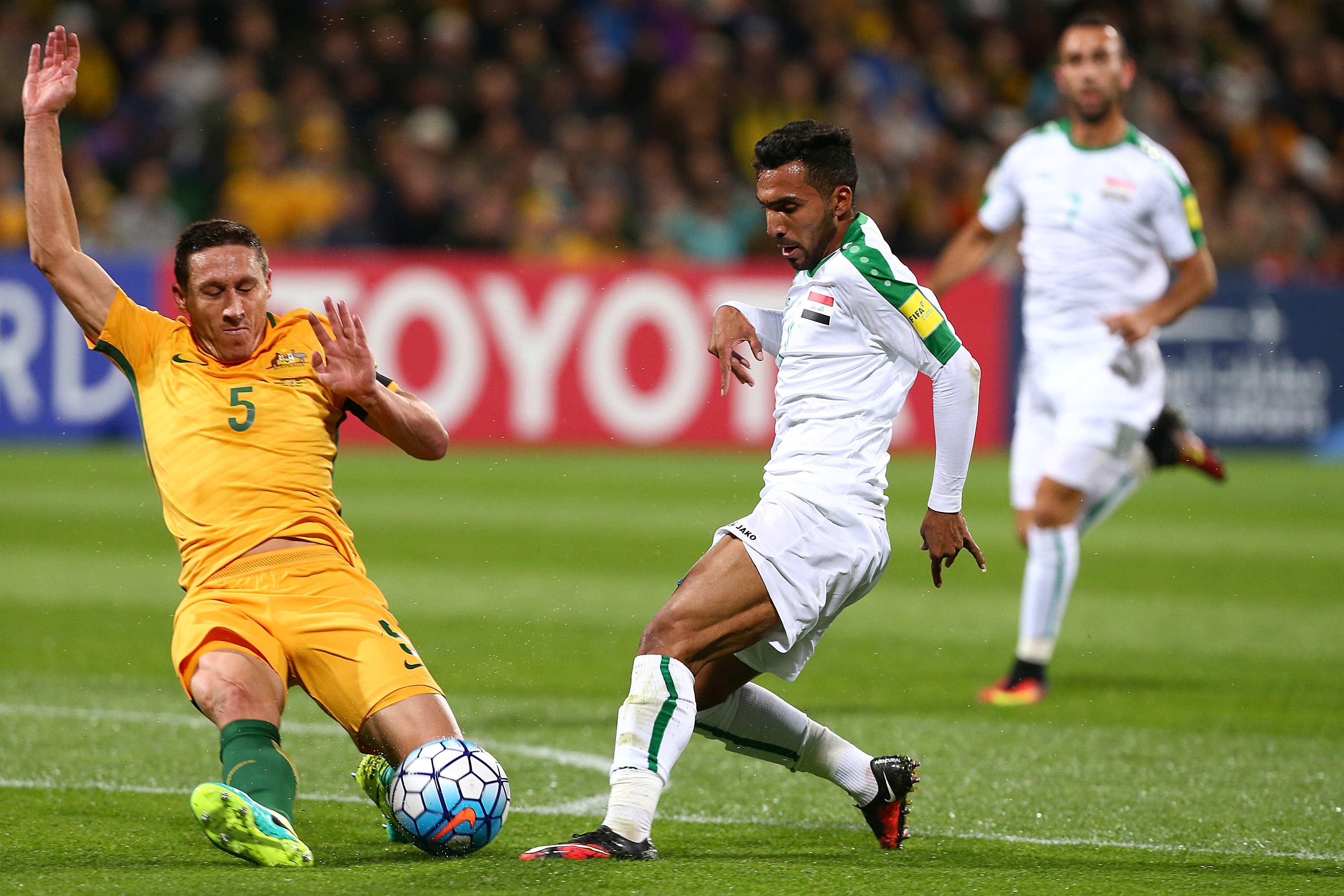Iraq threatened on the counter attack with Mark Milligan forced into a desperate challenge on Ali Hisny Faisal.