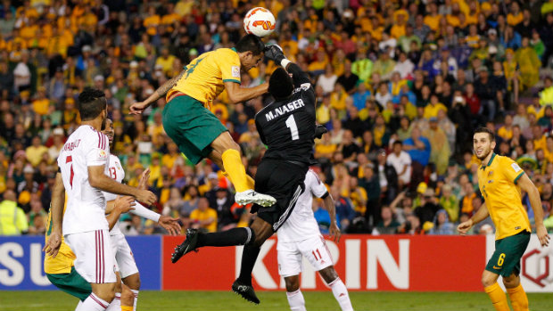 Tim Cahill flies high for a header against UAE goalkeeper Majed Naser.