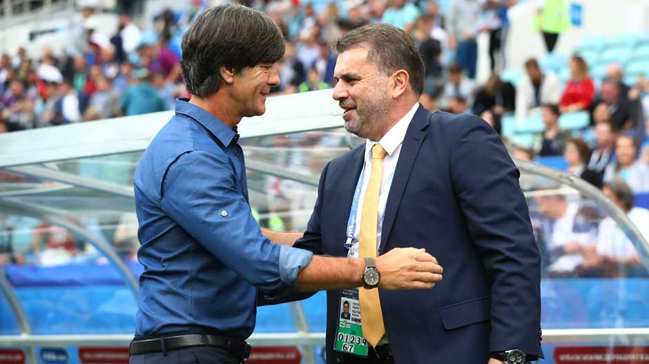Coaches Joachim Low and Ange Postecoglou exchange pleasantries before kickoff.