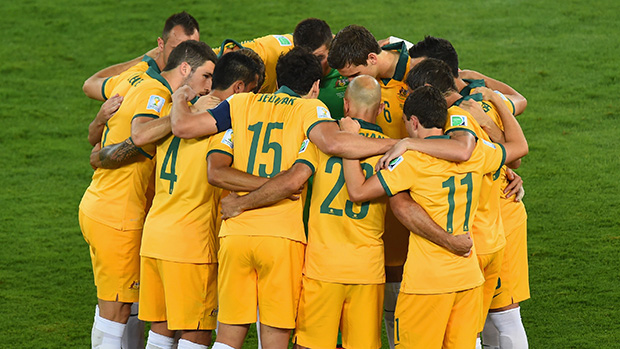 The Socceroos go into a huddle before kick-off against Chile.