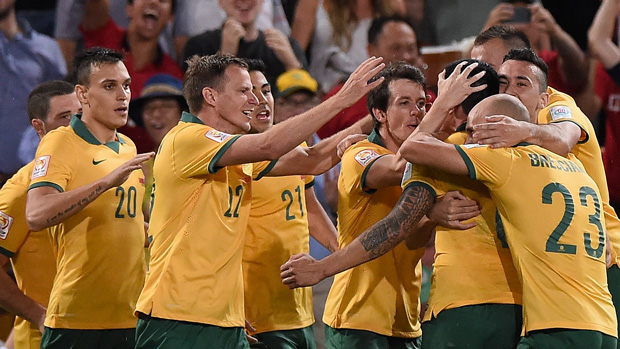Socceroos players celebrate one of Tim Cahill's two goals against China PR.
