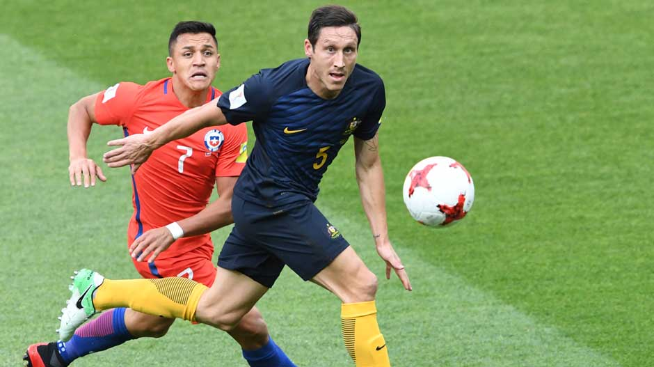 Caltex Socceroos defender Mark Milligan gets to the ball ahead of Chile's Alexis Sanchez.