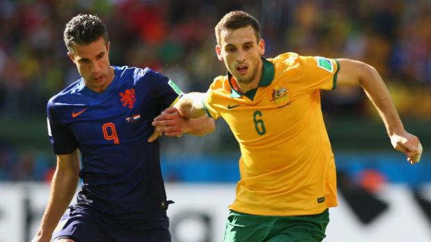 Socceroo Matt Spiranovic fends off the attention of the Netherland's Robin van Persie at the World Cup.