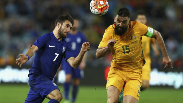 Caltex Socceroos skipper Mile Jedinak vies for the ball with Greek forward Giannis Gianniotas.