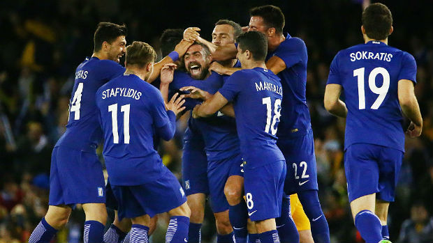 Greece players celebrate Iaonnis Maniatis' long range stunner against the Caltex Socceroos.