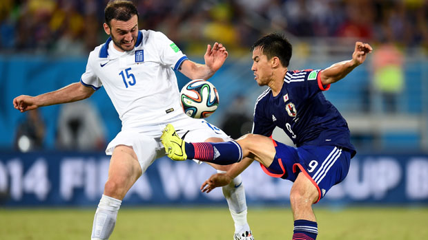 Vasilis Torosidis fights for the ball against Japan.