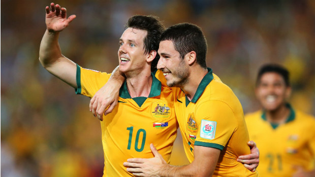 Robbie Kruse celebrates scoring against Oman with teammate Mathew Leckie.