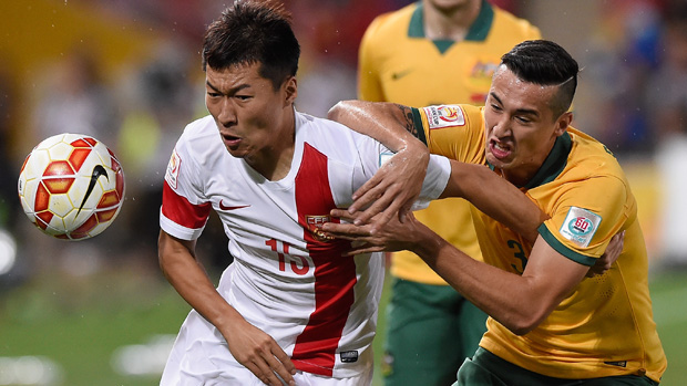 Wu Xi of China PR competes for the ball with Socceroos defender Jason Davidson.