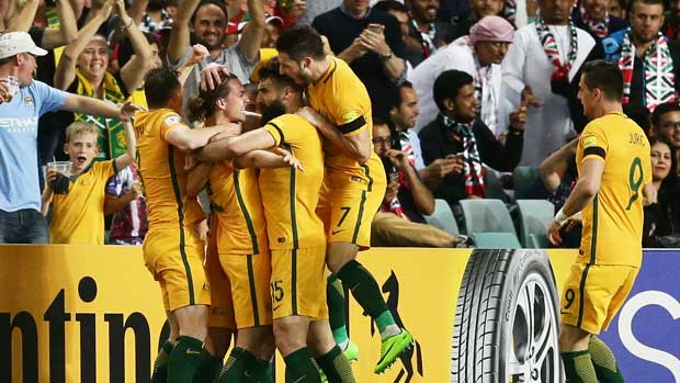 The Caltex Socceroos players swamp Jackson Irvine after his early goal in the win over UAE.