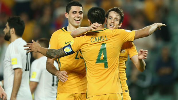 Socceroos Tim Cahill, Tom Rogic and Robbie Kruse celebrate opening the scoring against Jordan on Tuesday night.
