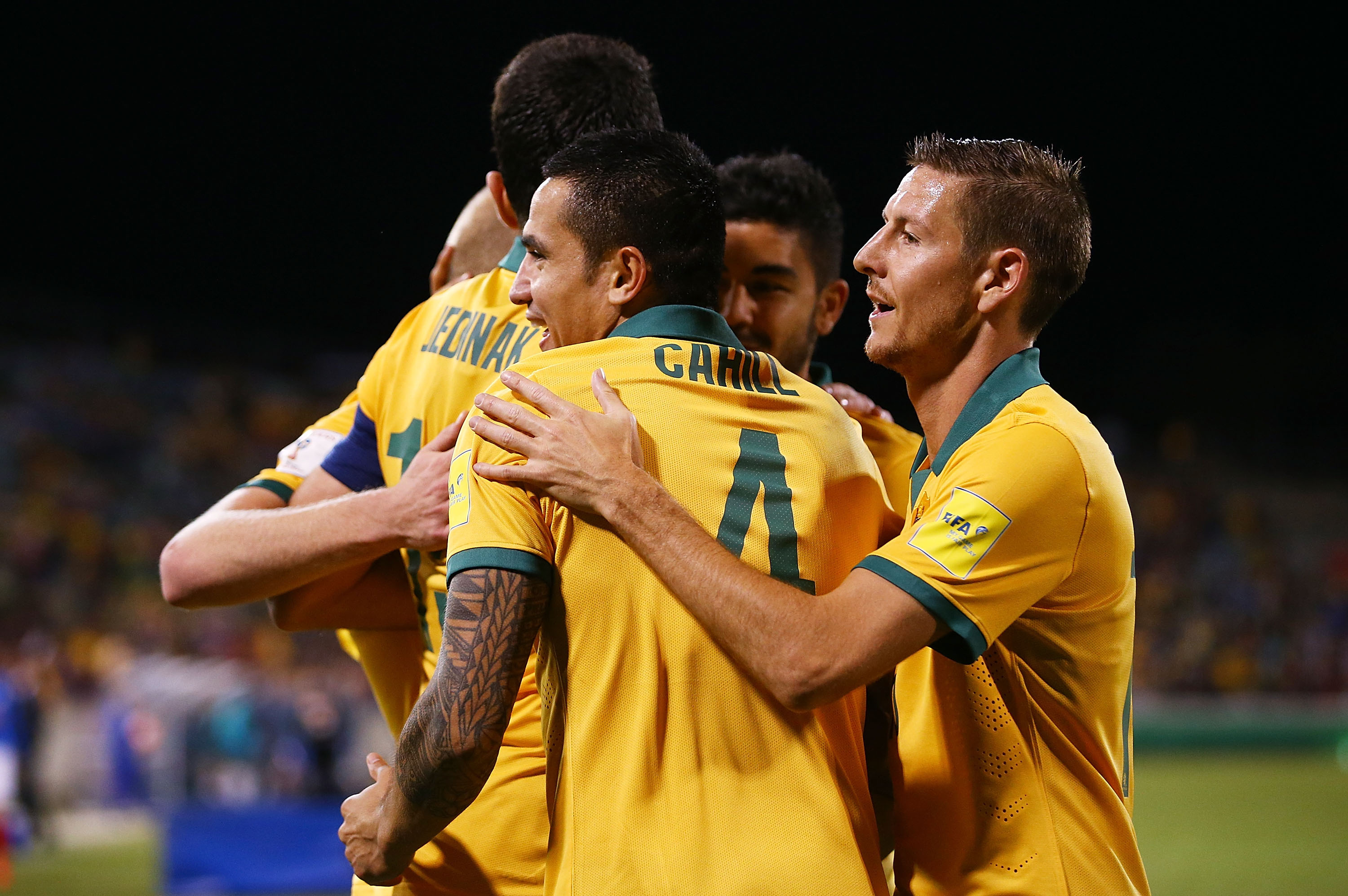 Tim Cahill celebrates with teammates after netting Australia's second goal against Kyrgyzstan in Canberra.