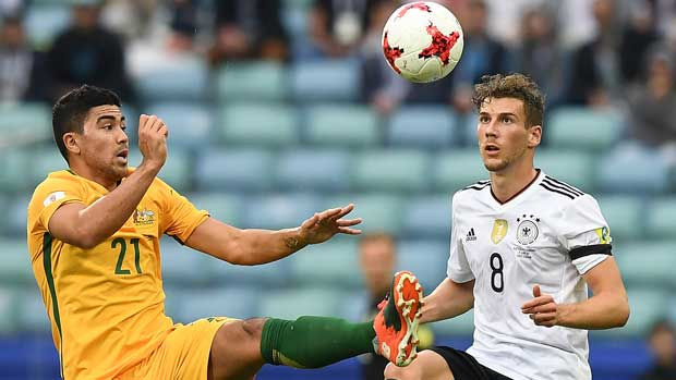 Caltex Socceroos midfielder Massimo Luongo fights for the ball with Germany's Leon Goretzka.