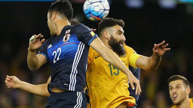 Mile Jedinak tussles for the ball with Japan's Maya Yoshida.