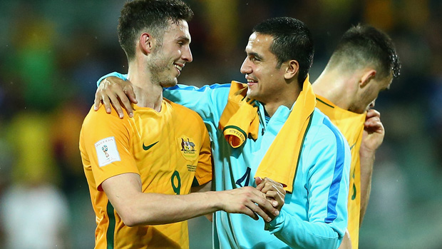 Apostolos Giannou is embraced by Socceroos talisman Tim Cahill following Australia's win over Tajikistan.