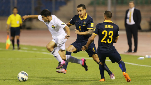 Tim Cahill and Tarek Elrich try to dispossess Jordan's Hamza Aldaradreh in Amman.