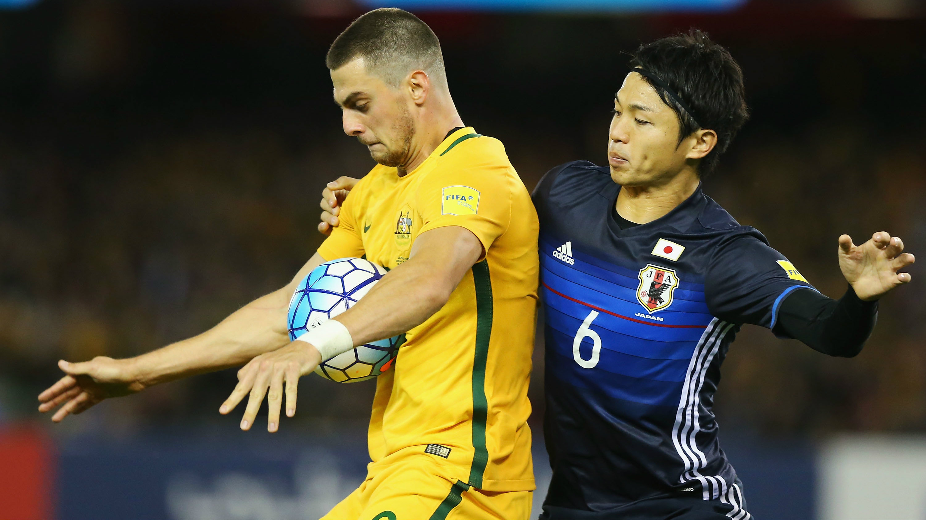 Tomi Juric of the Socceroos and Masato Morishige of Japan compete for the ball.