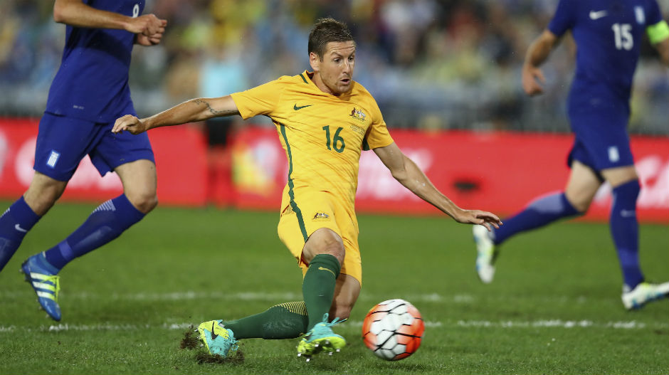 Caltex Socceroos forward Nathan Burns slips over on the ANZ Stadium surface as he's taking a shot on goal.