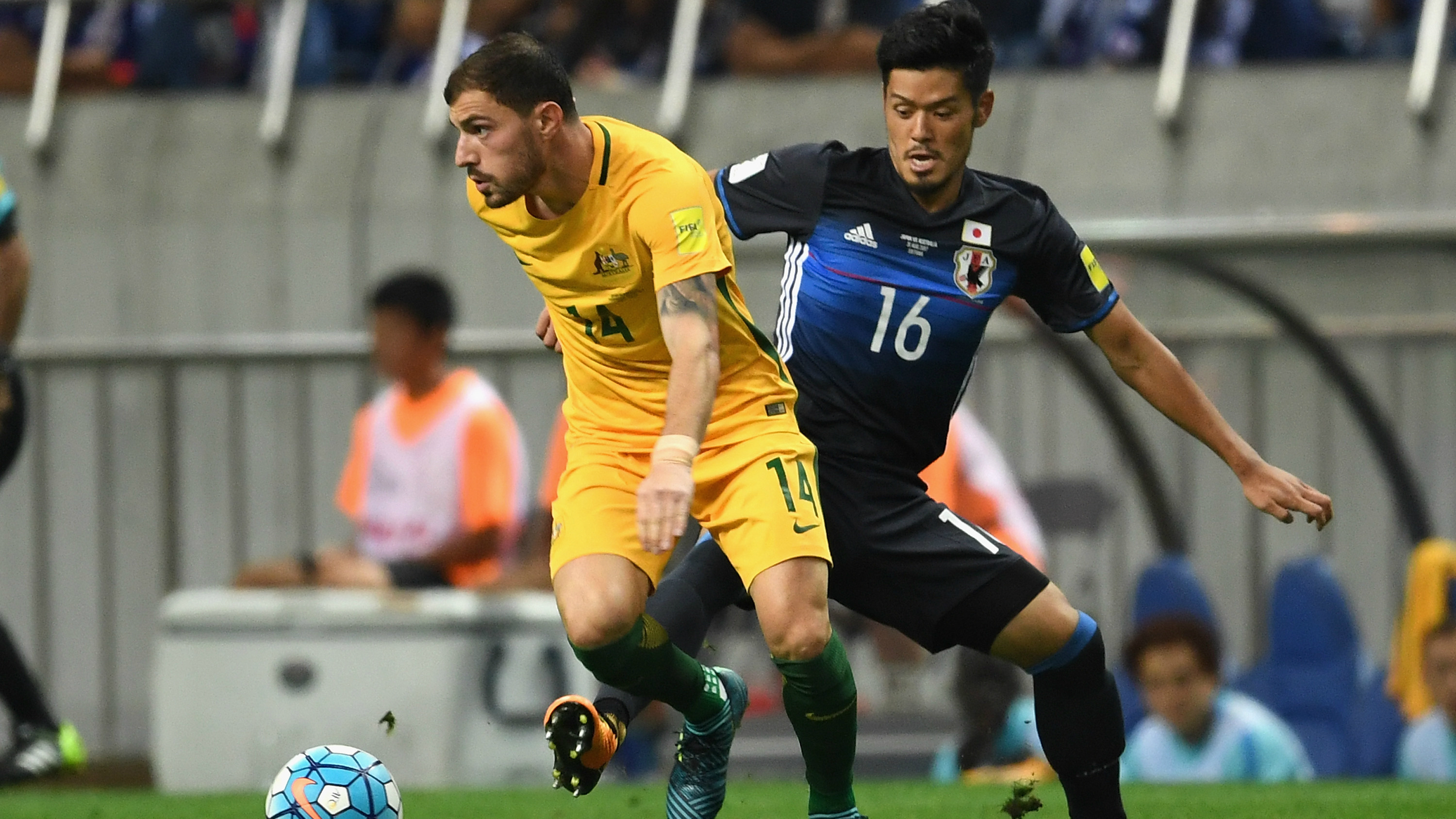 James Troisi looks to wriggle clear of his marker in Australia's 2-0 loss to Japan.