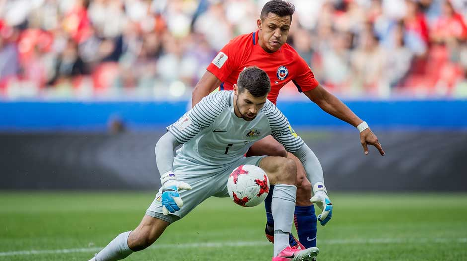 Goalkeeper Mat Ryan scoops on a loose ball just before Alexis Sanchez looks to pounce.