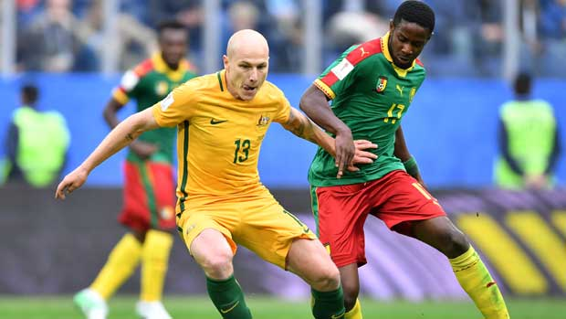 Caltex Socceroos midfielder Aaron Mooy holds off a Cameroon defender.