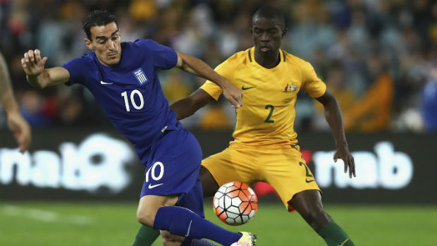 Defender Jason Geria make a challenge on Greek midfielder Lazaros Christodoulopoulos in his Caltex Socceroos debut.