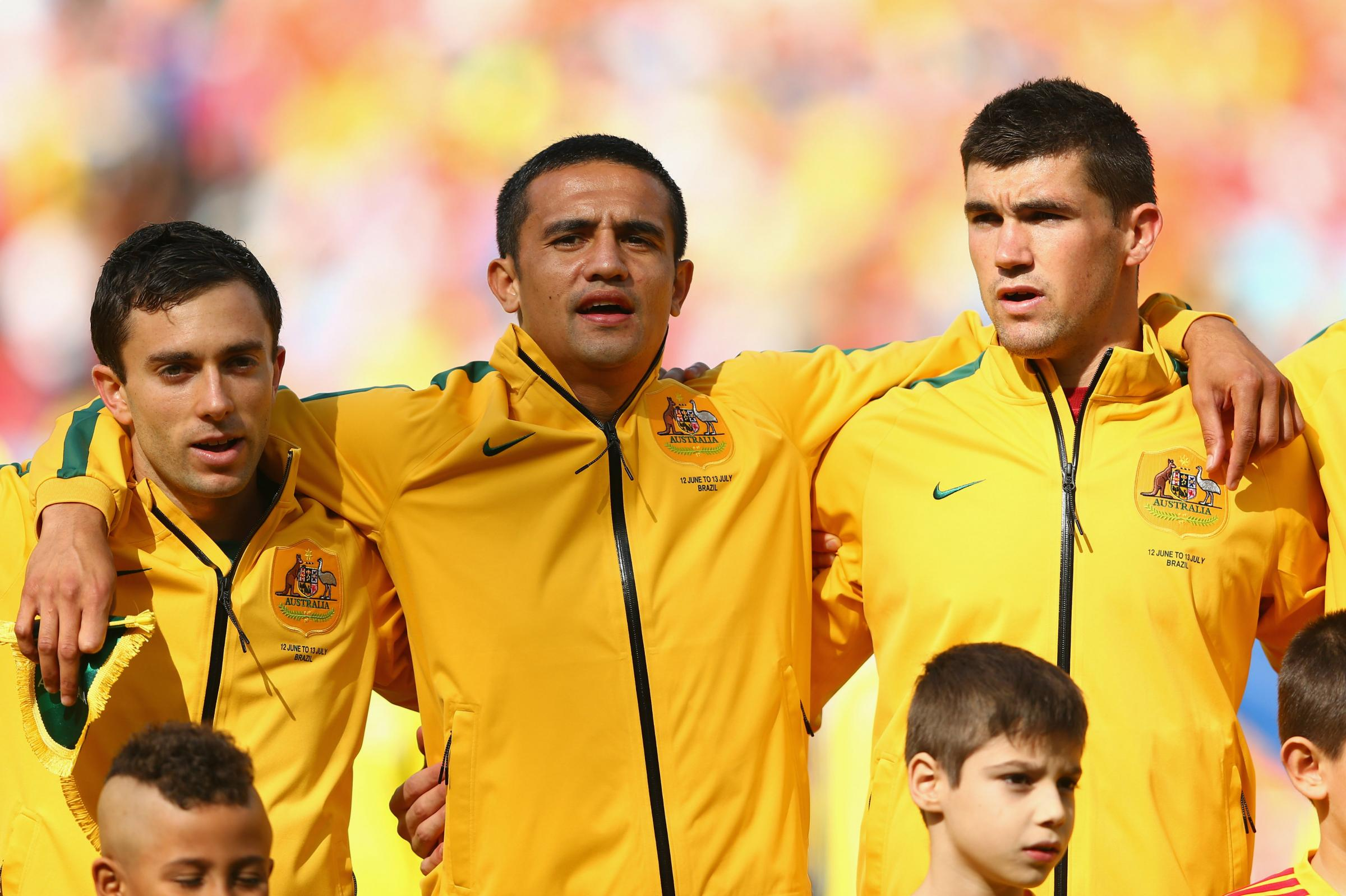 Tommy Oar alongside Tim Cahill and Mat Ryan during the national anthem.