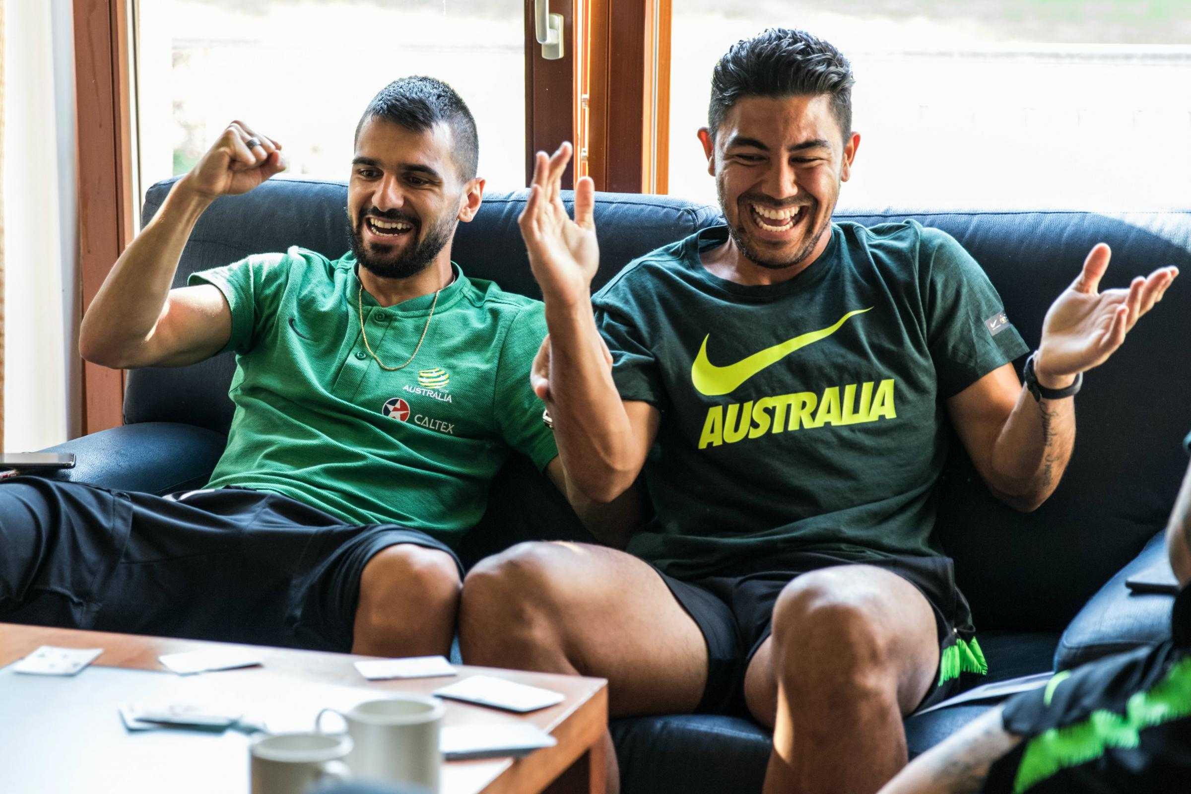 Aziz Behich and Massimo Luongo enjoy a game of cards in the team hotel.
