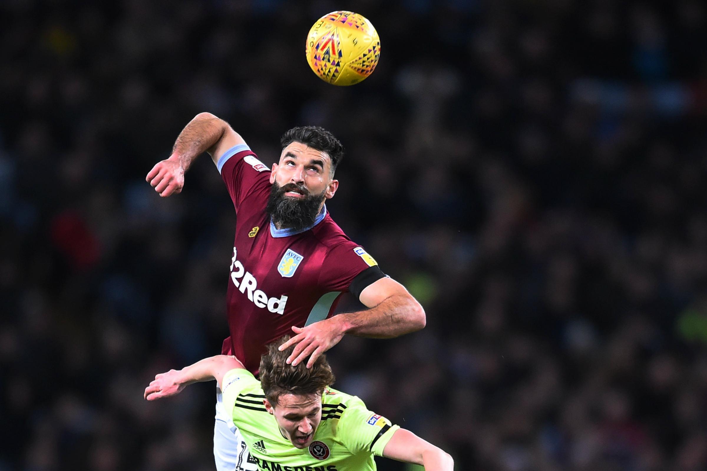 Mile Jedinak wins a header against Sheffield United