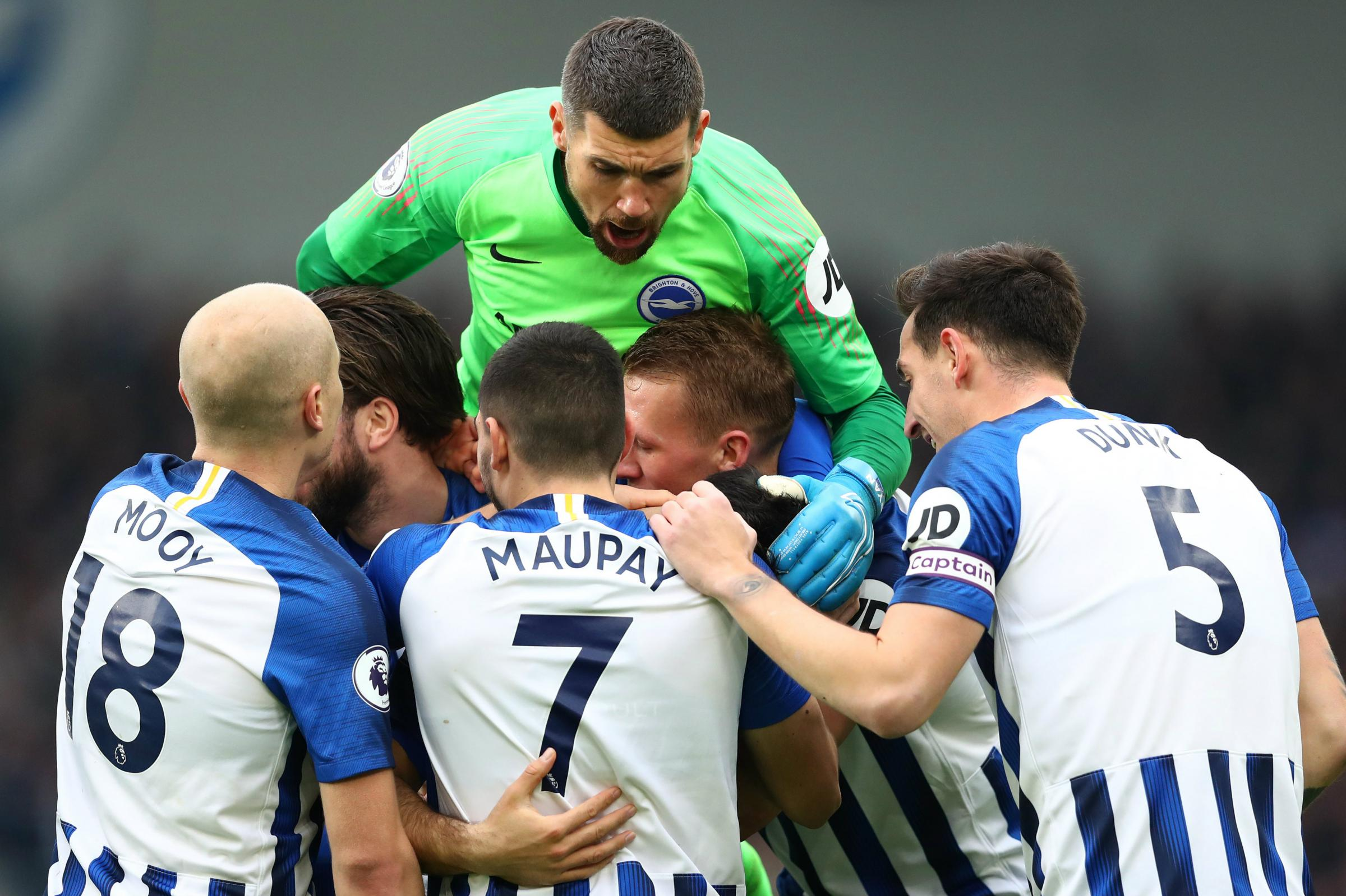 Maty Ryan and Aaron Mooy celebrate Brighton's first goal with teammates