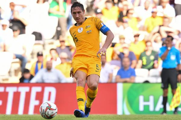Socceroos skipper Mark Milligan gets a pass away.