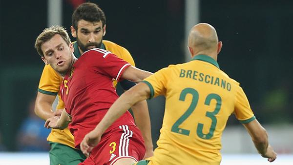 Mile Jedinak and Mark Bresciano challenge Belgium's Nicolas Lombaerts for the ball.