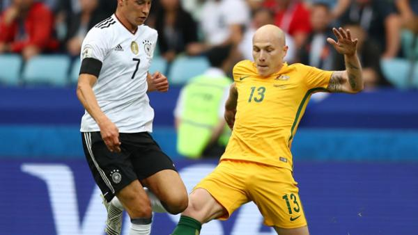 Aaron Mooy challenges for the ball with Germany's Julian Draxler.