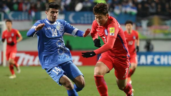 Son Heung Min of South Korea and Javokhir Sokhibov of Uzbekistan compete for the ball.