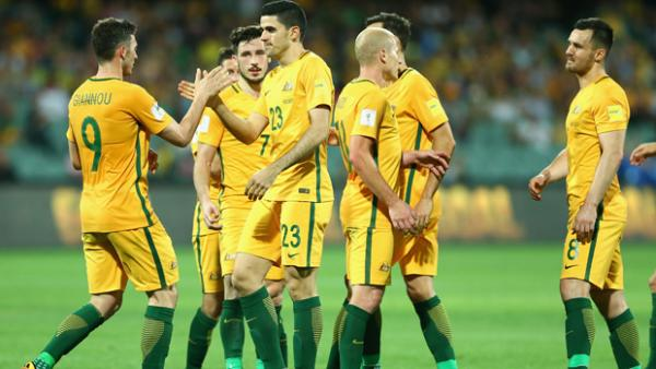 Tom Rogic celebrates with teammates after scoring against Tajikistan.