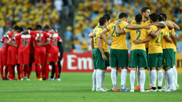 The Socceroos and Oman starting XI's form a huddle prior to kick-off at Stadium Australia.