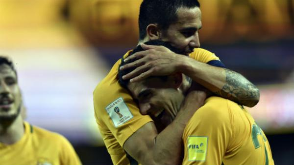 Tom Rogic receives a hug from Caltex Socceroos teammate Tim Cahill after scoring against Jordan.