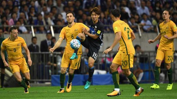 Four Caltex Socceroo surrond Japan attacker Yuya Osako.